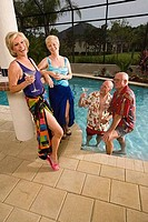 Portrait of senior women standing on poolside while senior men standing in swimming pool