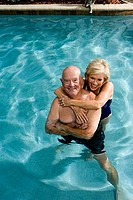 Cheerful senior couple embracing in swimming pool