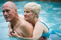 Close of a senior woman embracing a man in swimming pool