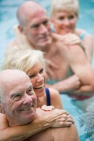 Close_up of senior women embracing senior men in a swimming pool