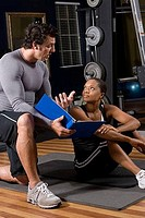 Trainer and a young woman engaged in conversion in the gym
