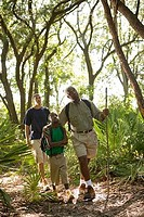 Mature man walking with his son and friend at forest