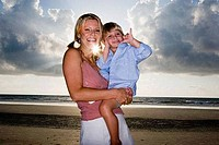 Cheerful young woman holding her son at the beach