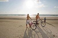 Portrait of a family with bicycles at the beach