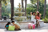 Young women sitting by water fountain while children with shopping bag