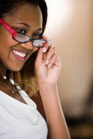 Cheerful businesswoman adjusting glasses