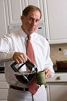 Portrait of a businessman pouring coffee into a coffee mug