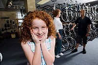 Girl smiling while her mother in conversation with cycle owner in a bicycle shop