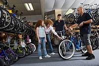 Girl with her mother looking at a bicycle in a bicycle shop