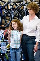 Girl with her mother in a bicycle shop