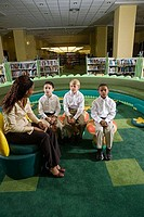 Teacher sitting with schoolboys on stools in the library