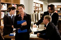 Businesswoman standing by table while colleagues discussing in background