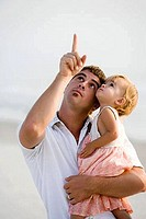 Young man with his daughter on the beach looking up