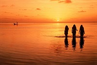 Silhouette three of people standing in sea at evening