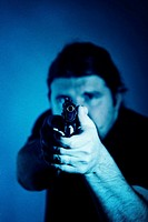 Portrait of a mid adult man aiming with a handgun