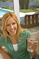 Happy young woman holding glass of water