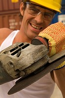 Portrait of a male dock worker holding a grinder (thumbnail)