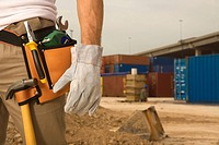 Mid section view of a construction worker wearing a tool belt