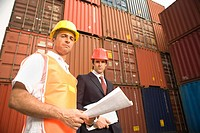 Portrait of a businessman and a dock worker standing in front of cargo containers