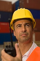 Close_up of a dock worker holding a walkie_talkie