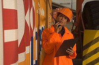 Mid adult woman using a walkie_talkie at a commercial dock