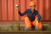 Mid adult woman sitting beside a railroad track and holding a hammer