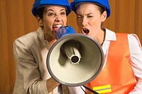 Two mid adult woman shouting into a megaphone