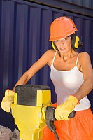 Portrait of a female dock worker holding a jackhammer