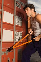 Dock worker cutting the bolt of a cargo container with a bolt cutter