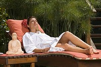Young woman in bathrobe and resting on a lounge chair in a health farm
