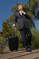 Low angle view of a businessman holding a luggage and walking