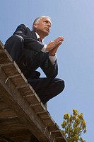 Low angle view of a businessman crouching in a prayer position on a boardwalk