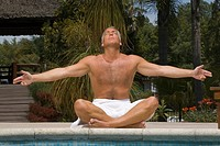 Mature man meditating at the poolside