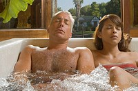 Close_up of a mature man and a young woman in a bathtub