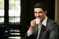 Portrait of a young man drinking a cup of tea and smiling (thumbnail)