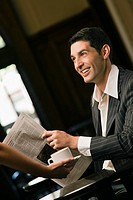 Side profile of a young man holding a newspaper and smiling