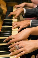 Close_up of people's hands playing a piano