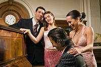 Side profile of a young man playing a piano and his friends looking at him (thumbnail)