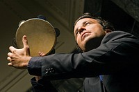 Side profile of a young man playing a tambourine
