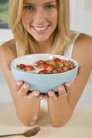 Close_up of young woman holding bowl of cereal