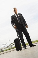 Portrait of a pilot standing holding his luggage (thumbnail)