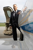 Portrait of a mature man at a vehicle door of a private airplane