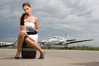 Portrait of a young woman sitting on her luggage at an airport
