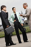Two businessmen and a businessman standing at an airport