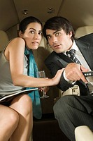Close_up of a businesswoman and a businessman looking surprised in a private airplane
