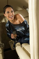 Businesswoman sitting in a private airplane and laughing
