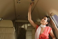 Businesswoman switching on light in a private airplane
