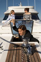 Businessman on boat with women behind (thumbnail)