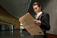 Young businesswoman reading newspaper (thumbnail)
