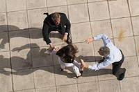 High angle view of businessmen fighting with businesswoman